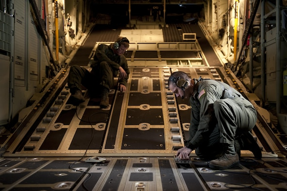 U.S. Air Force Senior Airmen Tim Manzer and Zach Harmon, 17th Special Operations Squadron MC-130J Commando II loadmasters, secure a cargo deck during a training exercise Feb. 17, 2016, off the coast of Okinawa, Japan. Manzer and Harmon participated in a 17th SOS simulation that tested the unit's ability to safely conduct a quick-reaction, full-force sortie involving a five-ship formation flight, cargo drops, short runway landings and takeoffs, and helicopter air-to-air refueling. (U.S. Air Force photo by Senior Airman Peter Reft/Released)