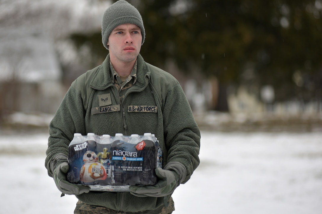Michigan Air National Guard Senior Airman Scott Lange, a member of the 127th Wing assigned to Selfridge Air National Guard Base, carries a case of water during water delivery efforts in Flint, Mich., Jan. 21, 2016. Selfridge Air National Guard Base has served as a hub for water distribution efforts in Flint. (U.S. Air National Guard photo)