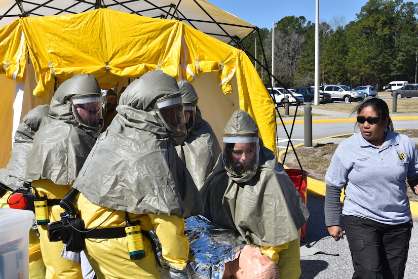 Staff members of Naval Health Clinic Charleston transport a simulated, contaminated patient through a decontamination tent during a timed Chemical, Biological, Radiological, Nuclear and Explosives exercise Feb. 18. NHCC's medical first responders practiced life-saving skills required to triage, initiate field treatment, decontaminate and save victims during a CBRNE event. From left to right: hospitalmen Seaman Apprentice Christopher Bishop, Petty Officer 2nd Class Jordan, Petty Officer 1st Class Terro Walker, Petty Officer 3rd Class Michael Boeji, Seaman Apprentice Brandy Sandoval; and Susan Osborne, a CBRNE instructor from DECON, LLC. (Navy photo by Petty Officer 3rd Class Robert Jackson)