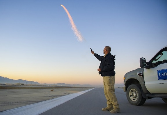 Wildlife biologist Scott Stopak, from the United States Department of Agriculture-Wildlife Services, fires off a pyrotechnic screamer on the flight line at Bagram Air Field, Afghanistan, Feb. 24, 2016. (U.S. Air Force photo by Capt. Bryan Bouchard)