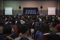 Students participating in the Central Intercollegiate Athletic Association (CIAA) High School Education Day grab their seats as Staff Sgt. Eric Rogers, canvassing recruiter from Recruiting Substation Charlotte, begins remarks at the Charlotte Convention Center on Feb. 24, 2016. High school students from around the Charlotte area participated in the event to learn about career and education opportunities. The Marine Corps has participated in CIAA events for more than 15 years and will be present for the 2016 CIAA basketball tournament. (Official Marine Corps Photo by Cpl. John-Paul Imbody)