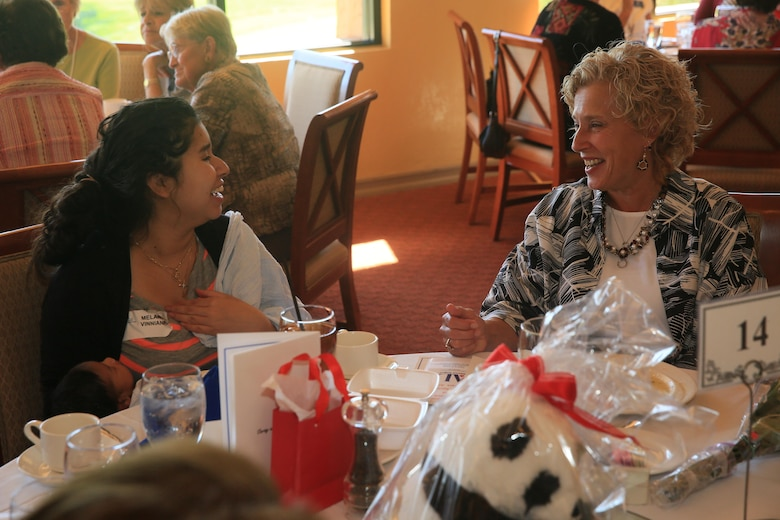 Laurie Craparotta, wife of Maj. Gen. Lewis A. Craparotta, Combat Center Commanding General, shares a laugh with Melanie Vinniane, wife of Sgt. Terrel Vinniane, motor transportation mechanic, 3rd Light Armored Reconnaissance Battalion, during the Assistance League of Palm Springs Desert Area Baby Shower Luncheon for Combat Center expectant mothers at the Oasis Country Club in Palm Desert, Calif., Feb. 16, 2016. (Official Marine Corps Photo by Cpl. Julio McGraw/Released)
