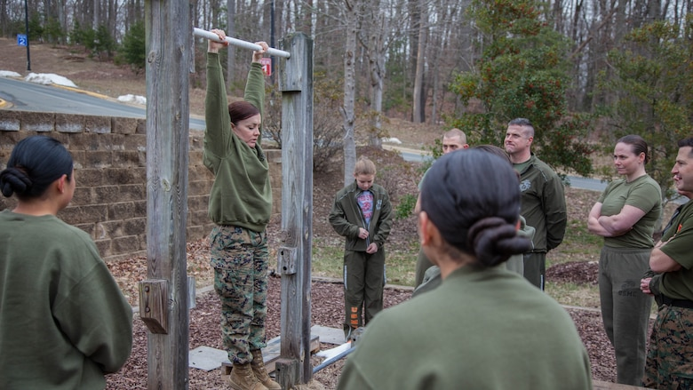 Major Misty Posey, center, demonstrates proper form for pull-ups to Marines at Marine Corps Base Quantico, Virginia, Feb. 19, 2016. Posey teaches a pull-up class at the James Wesley Marsh Center at MCB Quantico to improve the performance and capabilities of Marines for pull-ups according to Marine Corps fitness standards.  Posey is a plans officer for Manpower Integration.