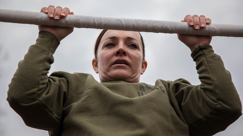 Major Misty Posey demonstrates proper form for pull-ups to Marines at Marine Corps Base Quantico, Virginia, Feb. 19, 2016. Posey, a plans officer for Manpower Integration, developed a pull-up program to assist Marines with their pull-ups and proper form.