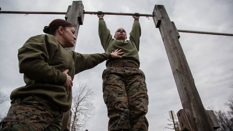 Major Misty Posey, left, assists a Marine doing pull-ups at Marine Corps Base Quantico, Virginia, Feb. 19, 2016. Posey teaches a pull-up class at the James Wesley Marsh Center at MCB Quantico to improve the performance and capabilities of Marines for pull-ups according to Marine Corps fitness standards. Posey is the plans officer for Manpower Integration.