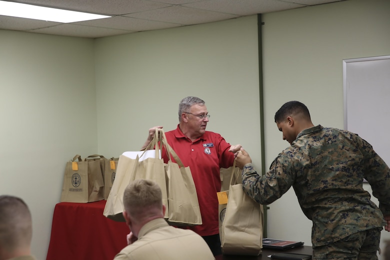Ray Caldwell, director of the Navy-Marine Corps Relief Society, Twentynine Palms Branch, gives the Combat Center Unit Representatives kits to begin the fund drive for their units at the Village Center, Feb. 19, 2016. (Official Marine Corps photo by Cpl. Thomas Mudd/Released)