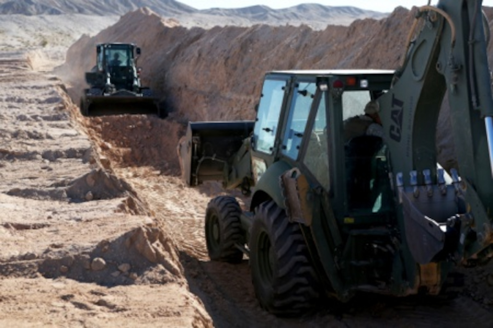 Heavy equipment operators with Headquarters and Support Company, Combat Logistics Battalion 5, 1st Marine Logistics Group, uses 420E Back Hoe create a 200 meter long defensive tank trench aboard Marine Corps Air Ground Combat Center Twentynine Palms, Calif., Feb. 8, 2016. Marines and Sailors with CLB-5 are participating in Integrated Training Exercise 2-16 in order to prepare their Marines for an upcoming deployment with Special Purpose Marine Air Ground Task Force – Crisis Response – Central Command, as well as increase the proficiency and capabilities of their unit as a whole.