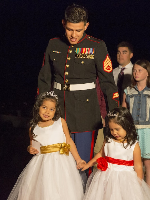 Staff Sgt. Guillermo Martinez, student, Marine Corps Communication-Electronics School, walks with his daughters during the Father Daughter Dance at Building 1707 Feb. 20, 2016. Marine Corps Community Services hosted the event to provide an opportunity for Marines and sailors to spend time with their daughters. (Official Marine Corps photo by Lance Cpl. Levi Schultz/Released)