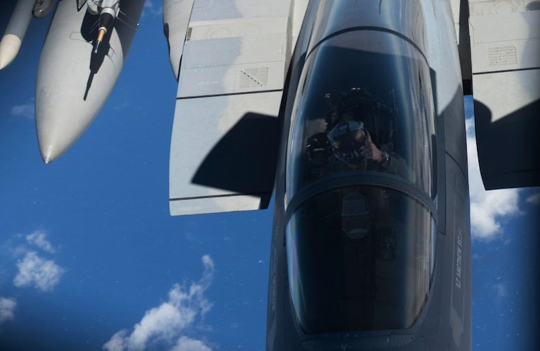 A 44th Fighter Squadron F-15 Eagle pilot signals completion of aerial refueling from a 909th Air Refueling Squadron KC-135 Stratotanker during the large force employment of exercise Cope North 16, Feb. 24, 2016, at Andersen Air Force Base, Guam. Through training exercises such as CN16, the U.S., Japan and Australian air forces develop combat capabilities, enhancing air superiority, electronic warfare, air interdiction, tactical airlift and aerial refueling. (U.S. Air Force photo by Staff Sgt. Matthew B. Fredericks/Released)