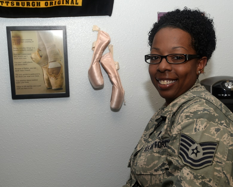 Technical Sgt. Niki Molinar, Paul W. Airey NCO Academy instructor, sits next to her ballet shoes posted on her office wall at the academy Feb. 24, 2016. Molinar credits much of her leadership ability to the discipline and creative skills she learned while teaching dance classes. (U.S. Air Force photo by Airman 1st Class Cody R. Miller/Released)