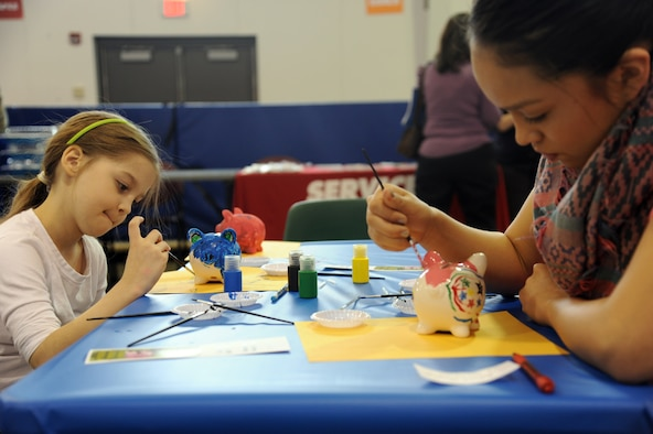 Daria McNerney, 8, and Nelenah Greyeyes, 15, paint piggy banks at the Military Saves Financial Fair on Grand Forks Air Force Base, N.D., Feb. 25, 2015. The fair was hosted by the Airman & Family Readiness Center and featured activities for children and helpful finance information for adults. (U.S. Air Force photo by Tech. Sgt. David Dobrydney/released)