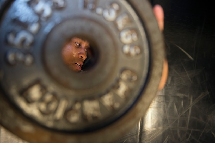 Senior Airman Jarred Alford, a Raven apprentice student, looks at an instructor while lifting weights during a three-week Phoenix Raven apprentice course Feb. 17, 2016 at Joint Base Charleston, S.C. Ravens are teams of specially trained security forces personnel dedicated to providing security for AMC aircraft transiting through high terrorist and criminal threat areas. (U.S. Air Force photo/Staff Sgt. Jared Trimarchi)