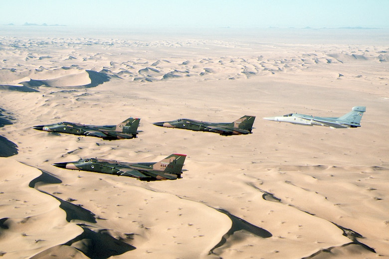 F-111F aircraft and an EF-111A Raven, rear, fly in formation over the desert during Operation Desert Shield. The aircraft are assigned to the 48th Tactical Fighter Wing. (Courtesy photo)