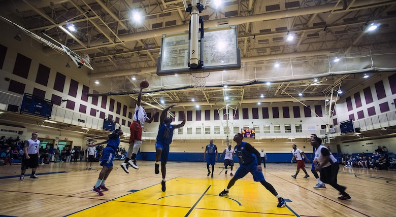 """The 8th Security Forces Squadron """"Defenders"""" (wearing blue) play against the 8th Fighter Wing Staff """"Agency"""" during an intramural basketball championship at Kunsan Air Base, Republic of Korea, Feb. 26, 2016. The Defenders beat the Agency 75-39. (U.S. Air Force photo by Staff Sgt. Nick Wilson/Released)"""