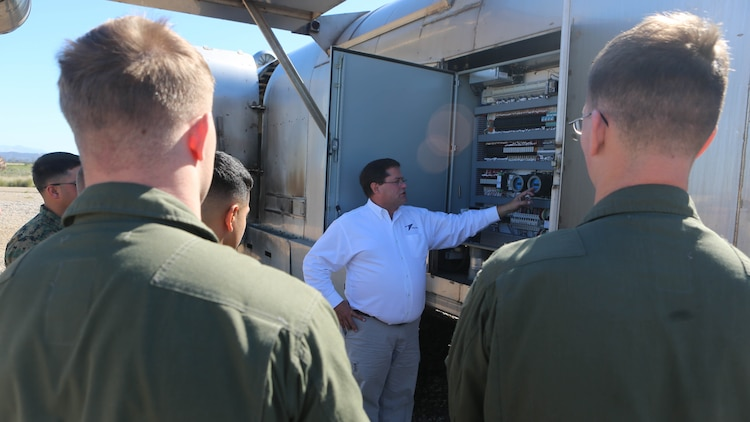 Greg Hudson, Mobile Aircraft Fire Training Device program manager and an Orlando, Florida, native, talks to the Marines about the functions of the Mobile Aircraft Fire Training Device aboard Marine Corps Air Station Miramar, California, Feb. 22. The MAFTD is a computer-operated device and the different functions are controlled via a panel. The MAFTD is used by Aircraft Rescue and Firefighting Marines to conduct live-fire training.