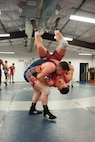 Airman 1st Class Tyler Westlund, from Wright-Patterson Air Force Base, Ohio, takes 1st Lt. Brandon Mueller, from Kirtland AFB, N.M., to the mat during their six-week training camp at Joint Base McGuire-Dix-Lakehurst, N.J. (U.S. Air Force photo/Christian DeLuca)