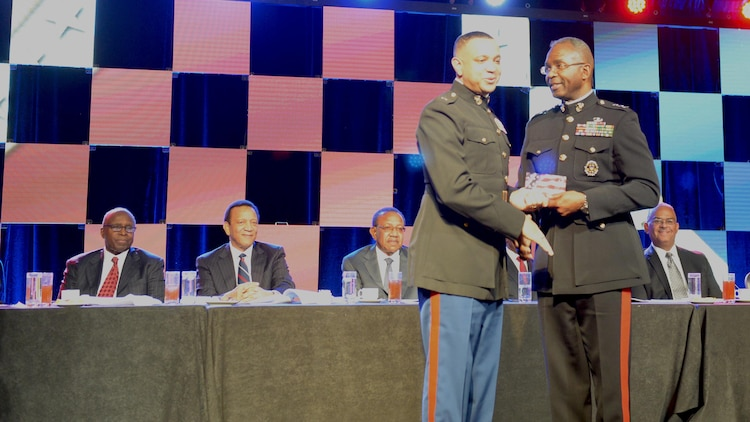 "Lt. Col. David Everly, junior military assistant to the Secretary of Defense, is presented an award at the Black Engineer of the Year 11th Annual Stars and Stripes Dinner Feb. 19, 2016 at the Philadelphia Marriott Downtown Grand Ballroom in Philadelphia by Lt. Gen. Ronald Bailey, the Deputy Commandant Plans, Polices and Operations at Headquarters Marine Corps. ""If you're looking for excellence in military hands-on experience, look no further than Lt. Col. Dave Everly,"" said Bailey. ""Lt. Col. Everly epitomizes our values of courage, honor and commitment as a role model and a mentor."""