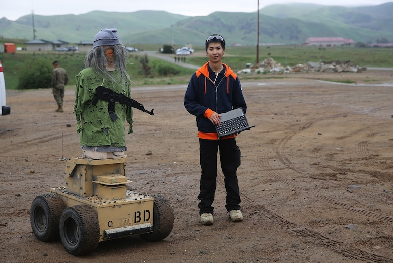 Nathan Fung poses with an Autonomous Robotic Human Type Target Feb. 18, at Camp Pendleton. Marines from Division Schools 1st Marine Division tested the targets to see if they could use them to evolve their training by creating more realistic, less predictable scenarios. Fung, a robotics engineer for Marathon Targets, is a native of Sydney, Australia. (U.S. Marine Corps Photo by Cpl. John Baker)