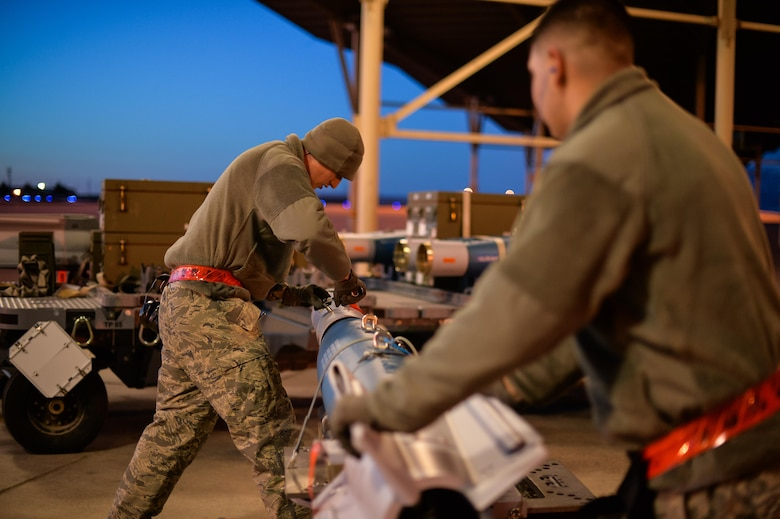 Staff Sgt. Jeffrey Kalsbeek and Airman Juan Rivas, 34th Aircraft Maintenance Squadron load crew members, prepare to equip an F-35A with a GBU-12 laser-guided bomb at Hill Air Force Base, Utah, Feb. 23, 2016. (U.S. Air Force photo by R. Nial Bradshaw)