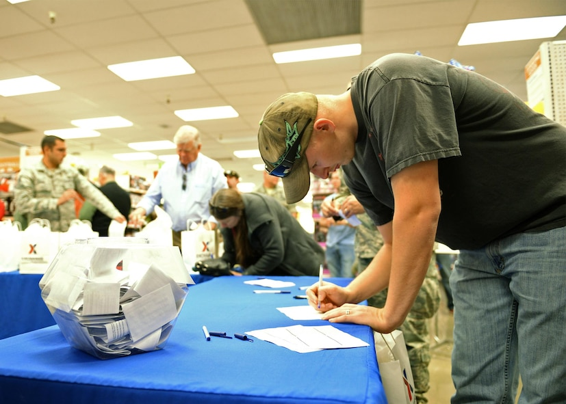 Senior Airman Austin Kauffman enters a raffle during the grand re-opening of the newly renovated Base Exchange Feb. 25, 2016, Beale Air Force Base, California. The remodeling project cost approximate$1.9 million, which includes new flooring, a floor plan to accommodate an expanded product line, new displays, and a new central checkout location. (U.S. Air Force photo by Robert Scott)