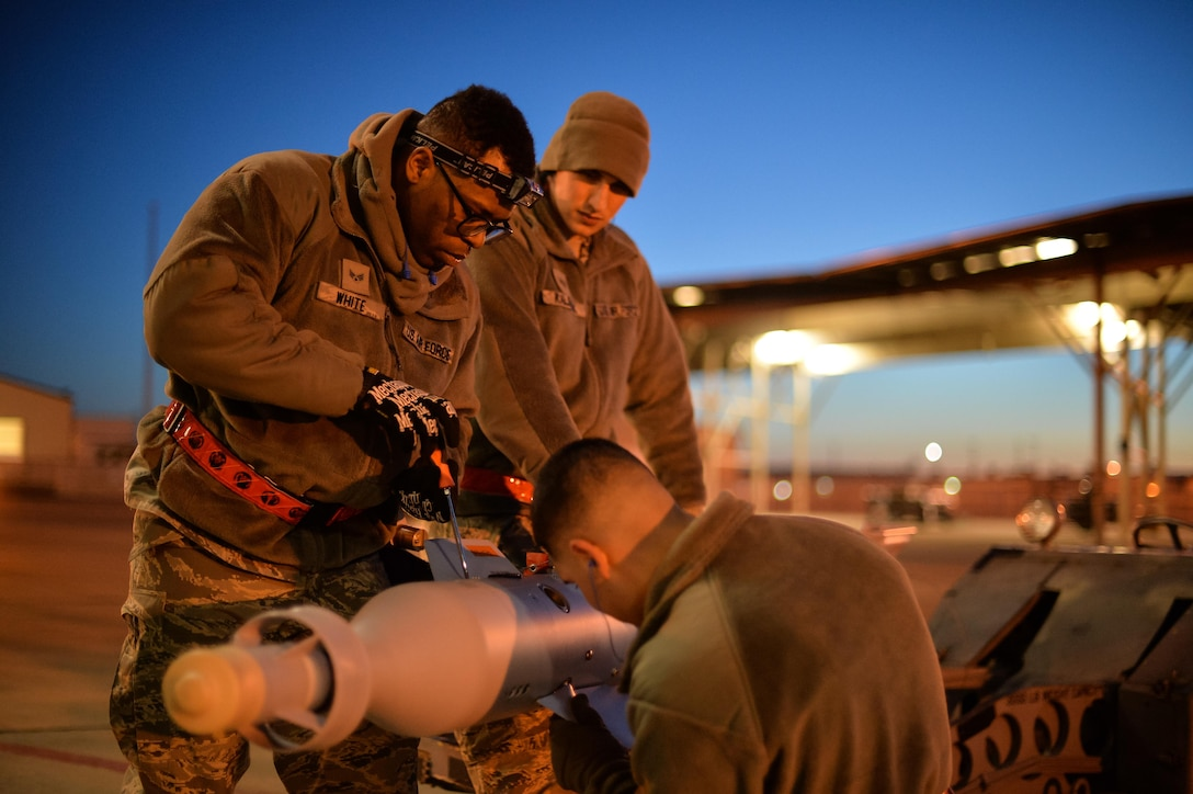 Airman Juan Rivas, Senior Airman Darion White and Staff Sgt. Jeffrey Kalsbeek, 34th Aircraft Maintenance Squadron load crew members, prepare to equip an F-35A with a GBU-12 laser-guided bomb at Hill Air Force Base, Utah, Feb. 23, 2016. (U.S. Air Force photo by R. Nial Bradshaw)