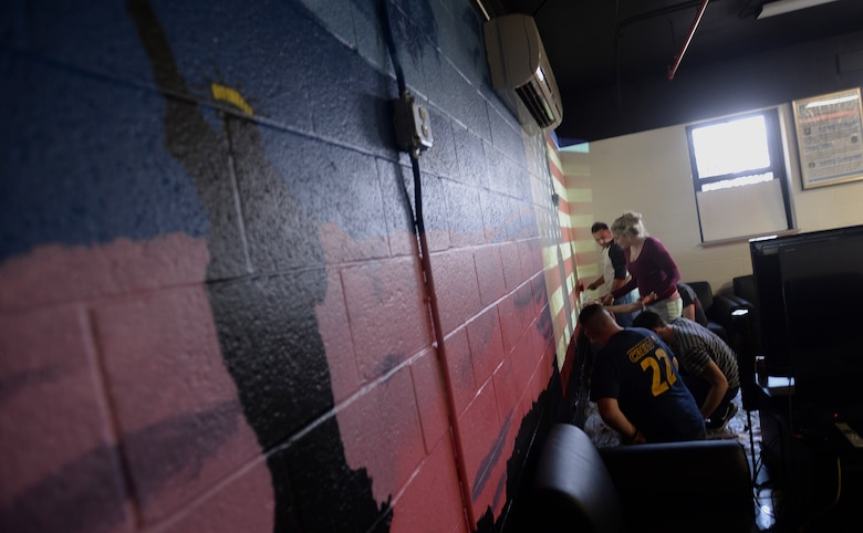 """Members of the Airman Ministry Center, or the """"Den"""", paint a mural on the interior walls of the room, Feb. 13, 2016, at McConnell Air Force Base, Kan. The mural was started on Feb. 6 and is set to be finished the first week of March. (U.S. Air Force photo/Senior Airman Colby L. Hardin)"""