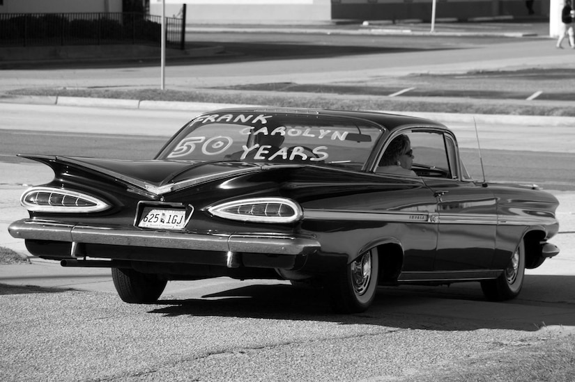 Frank Metzger, a 437th Airlift Wing program analyst, drives away in a 1959 Chevrolet Impala with his wife, Carolyn, after renewing their wedding vows for their 50th anniversary, Oct. 5, 2013. Carolyn surprised Metzger with the car upon leaving the ceremony; it was the same year and model as the one he drove when they were dating. (Courtesy Photo)