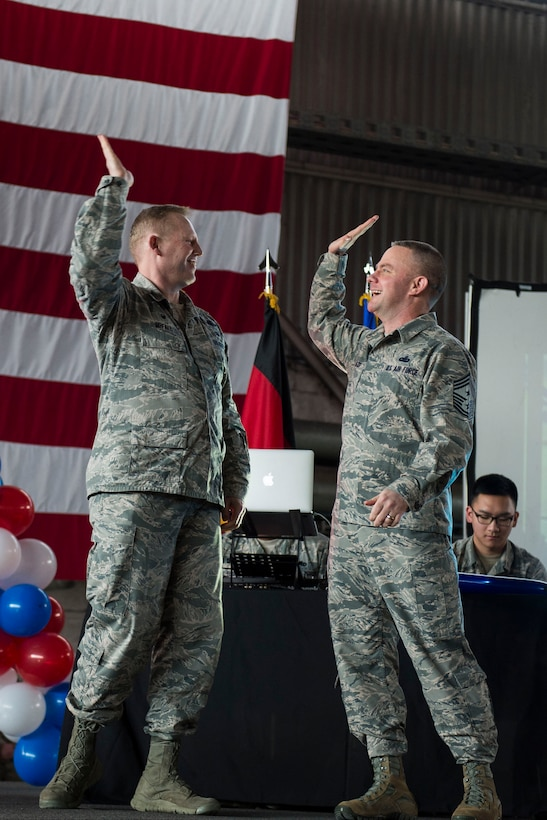 U.S. Air Force Col. Joe McFall, 52nd Fighter Wing commander, left, celebrates with U.S. Air Force Chief Master Sgt. Brian Gates, 52nd FW command chief, during the Year in Review Pep Rally in Hangar 1 at Spangdahlem Air Base, Germany, Feb. 25, 2016. McFall and Gates handed out jerseys to the 52nd Fighter Wing 2015 annual awards nominees to recognize their accomplishments. (U.S. Air Force photo by Airman 1st Class Luke Kitterman/Released)