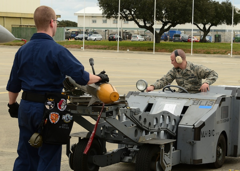 Senior Airman Noah Fuller and Airman 1st Class Edward McGroder, 493rd Aircraft Maintenance Unit weapons load crew members, transport simulated munitions on an MJ-1 Lift Truck during exercise Real Thaw at Beja Air Base, Portugal, Feb. 25, 2016. Real Thaw was designed to provide joint interoperability training throughout the execution of a vast range of battlefield missions, to include day and night operations in a high-intensity joint setting. (U.S. Air Force photo by Senior Airman Dawn M. Weber/Released)