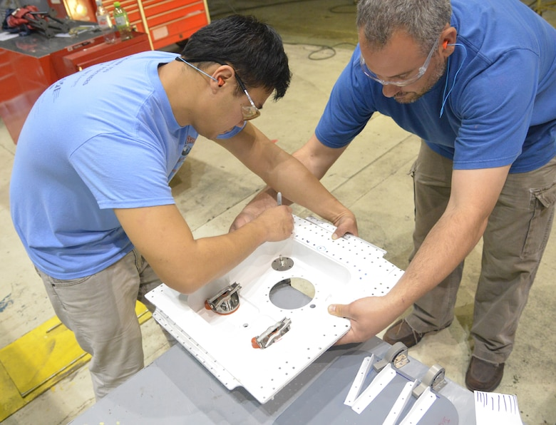 Terry Li, 402nd Aircraft Maintenance Support Squadron aircraft engineering supervisor, works on a waste service pan with Shawn Coffee, 562nd Aircraft Maintenance Squadron aircraft sheet metal worker. (U.S. Air Force photo by Ray Crayton)