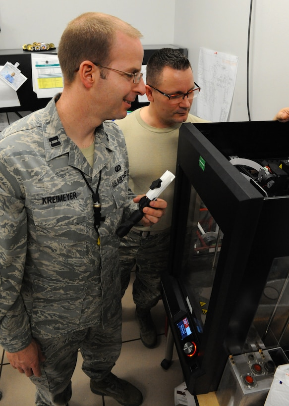 """U.S. Air Force Capt. Wayne Kreimeyer, the 509th Maintenance Group (MXG) Research and Engineering (RE) flight commander, right, reviews the progress of a 3-D print with Master Sgt. James Gargano, an RE technician with the 509th MXG, at Whiteman Air Force Base, Mo., Feb. 18, 2016. The 3-D model is used for """"form-fit function."""" The form-fit function method prints an object for specification prior to sending to the metals technology shop for fabrication. (U.S. Air Force photo by Tech. Sgt. Miguel Lara III)"""