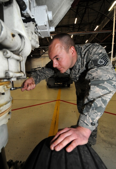 U.S. Air Force Tech Sgt. Aaron Bradley, a 393d Aircraft Maintenance Unit specialist section chief, uses a socket wrench to adjust the front landing gear of a B-2 Spirit at Whiteman Air Force Base, Mo., Feb. 18, 2016. When needed, Bradley wears a headset to communicate with a second member in the cockpit—who applies hydraulic pressure. This method allows the crew to adjust the steering of the front landing gear without actually turning the wheel, which prevents wear on the tires. (U.S. Air Force photo by Tech. Sgt. Miguel Lara III)