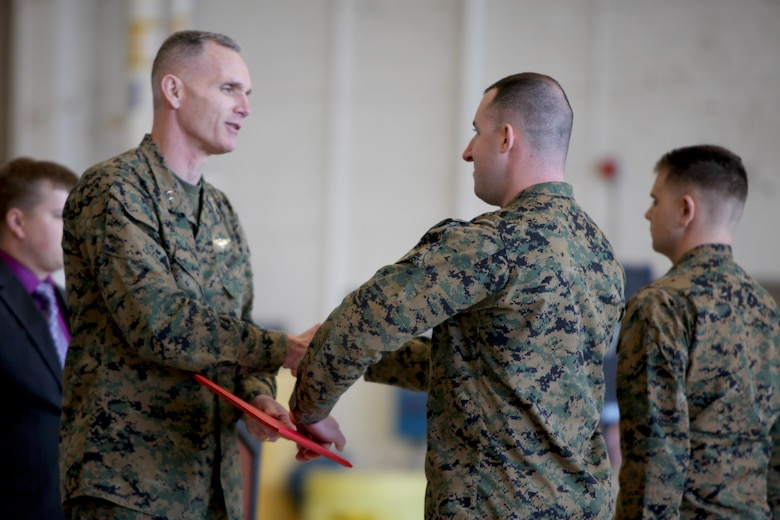 Maj. Gen. Gary L. Thomas congratulates and hands Sgt. Eric Foldvary a certificate of course completion at the conclusion of a Squadron Intelligence Training and Certification Course at Mid Atlantic Electronic Warfare Range, N.C., Feb. 12, 2016. To date, the course has certified more than 300 Marines enabling them to better integrate into the Marine Air-Ground Task Force. Thomas is the commanding general of 2nd MAW, Foldvary is an intelligence specialist with Marine Aircraft Group 14.  (U.S. Marine Corps photo by Cpl. Jason Jimenez/Released)