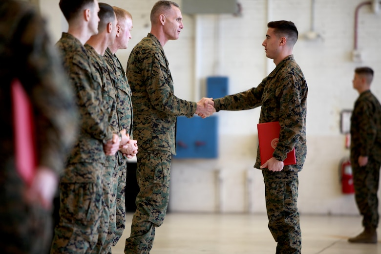 Maj. Gen. Gary L. Thomas congratulates Lance Cpl. Kurt Bright during a graduation ceremony at the conclusion of a Squadron Intelligence Training and Certification Course at Mid Atlantic Electronic Warfare Range, N.C., Feb. 12, 2016. To date, the course has certified more than 300 Marines enabling them to better integrate into the Marine Air-Ground Task Force. Thomas is the commanding general of 2nd MAW and Bright is an intelligence specialist with Marine Light Attack Helicopter Squadron 269. (U.S. Marine Corps photo by Cpl. Jason Jimenez/Released)