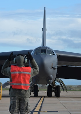 A crew chief from the 2nd Expeditionary Bomb Group guides a B-52 Stratofortress into its parking spot at Morón Air Base, Spain, Feb. 27, 2016. This B-52 and two others will join KC-135 Stratotankers and F-16 Fighting Falcons as the U.S. air component during Cold Response 16, a biennial NATO military exercise. Participants will experience sub-freezing temperatures in the Trøndelag region of Norway over the course of the nearly two-week exercise. (U.S. Air Force photo/Senior Airman Joseph Raatz)