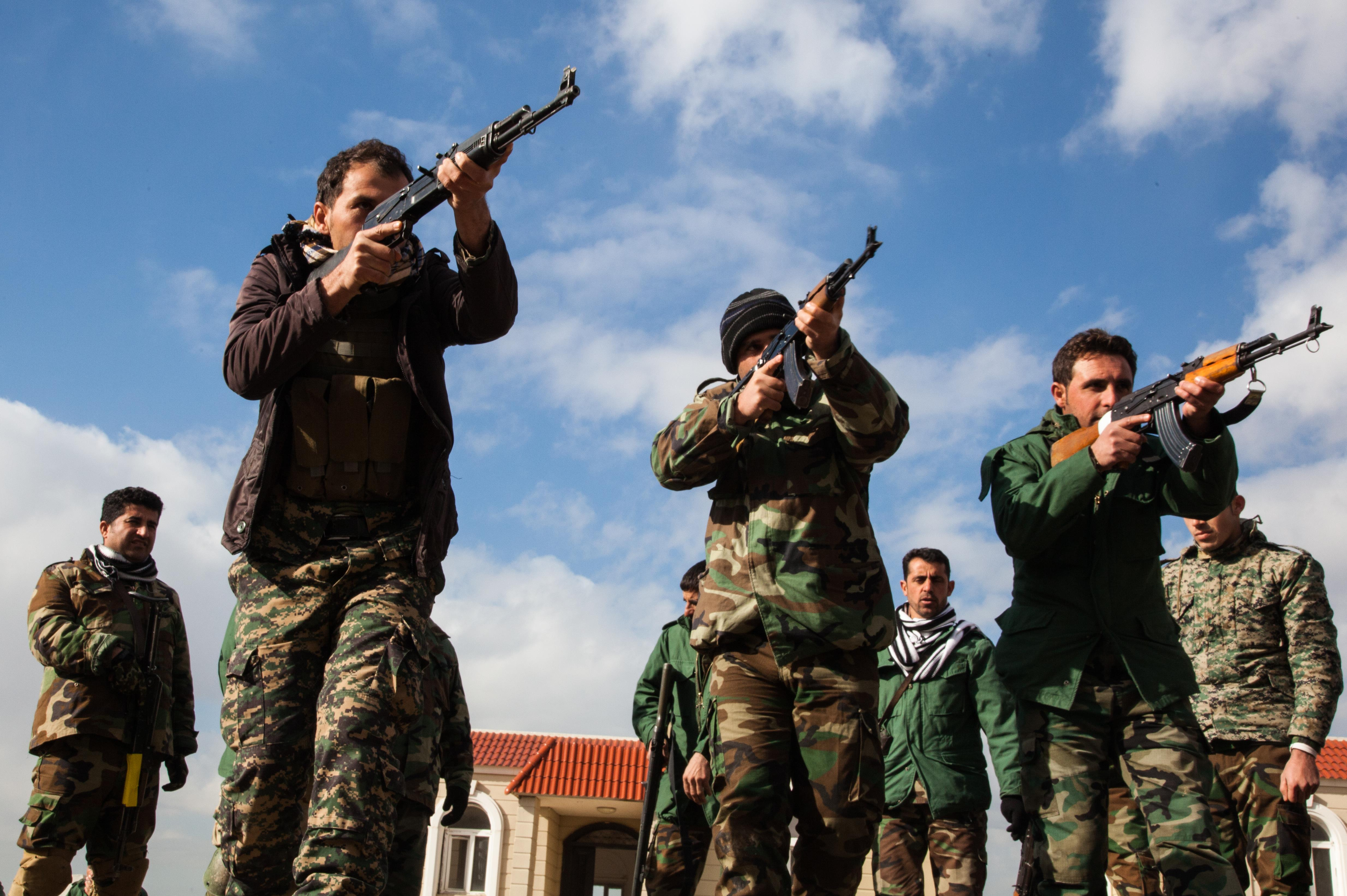 Peshmerga soldiers practice tactical movements and clearing a buildings