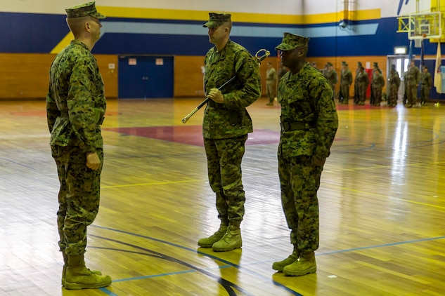 Sgt. Maj. Coleman Kinzer, left, outbound Headquarters and Headquarters Squadron sergeant major, prepares to pass on the sword of office to Sgt. Maj. Darnell Richardson, right, newly appointed H&HS sergeant major, during a relief and appointment ceremony at Marine Corps Air Station Iwakuni, Japan, Feb. 26, 2016. The passing of the sword of office represents the transition of duties and responsibilities from one sergeant major to another. Kinzer addressed the Marines of the squadron, stating that he believes without them, the transformation of the air station wouldn't be possible.