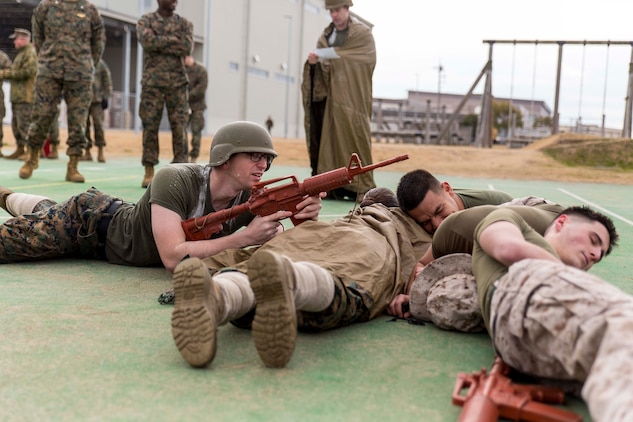 Marines with the provost marshal's office accident investigation department demonstrate professional military education during the Frozen Chosin Competition at Marine Corps Air Station Iwakuni, Japan, Feb. 25, 2016. Teams consisting of six members completed a series of events including a pull up and sit up contest, a 5k supply run, a 600 meter swim, 250 meter sprint then constructing and presenting a PME. By testing physical endurance and strength throughout multiple consecutive events, the competition helps build morale, confidence and esprit de corps within the squadron.