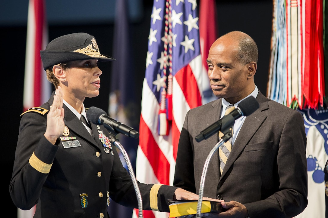 U.S. Army Lt. Gen. Nadja West takes the oath of office after promotion to her current rank as her husband, retired U.S. Army Col. Donald West, holds a Bible during the Feb. 9 ceremony on the Fort Myer portion of Joint Base Myer-Henderson Hall. West was promoted and sworn in by U.S. Army Chief of Staff Gen. Mark A. Milley. West is the Army's 44th surgeon general and commanding general for U.S. Army Medical Command. (Joint Base Myer-Henderson Hall PAO photo by Nell King)