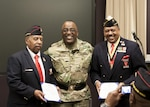 DLA Distribution commander, Army Brig. Gen. Richard B. Dix, center, presents star notes to Retired Marine Sgt. Henry N. Wilcots, left, and Retired Marine Master Gunnery Sgt. Joseph H. Geeter, III, right, during the Black History Month presentation in New Cumberland, Pa., on Feb. 24.
