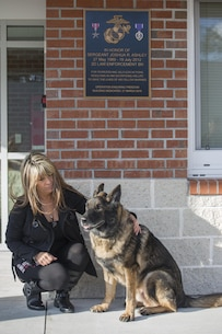 Tammie Ashley sits outside of the 2nd Law Enforcement Battalion kennels with her son's former Military Working Dog, Sirius, at Camp Lejeune, N.C., Feb. 25, 2016. Tammie's son and Sirius' former handler, Sgt. Joshua Ashley, was killed while on patrol in 2012 in support of Operation Enduring Freedom. The Ashley family adopted Sirius after a passing of the leash retirement ceremony. (U.S. Marine Corps Photo by Lance Cpl. Erick Galera/Released.)