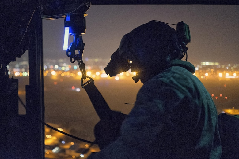 Tech. Sgt. Michael Wright, 459th Airlift Squadron UH-1N Huey flight engineer, reels in a UH-1N hoist cable at Yokota Air Base, Japan, Feb. 23, 2016. For 459th AS special missions aviators to become certified to operate the hoist, SMA instructors with the 512th Rescue Squadron, Kirtland AFB, New Mexico, and the 36th RQS, Fairchild AFB, Washington, arrived at Yokota to train alongside flight engineers. The requalification process included day and night hoist operations with instructor supervision. (U.S. Air Force photo by Airman 1st Class Delano Scott/Released)