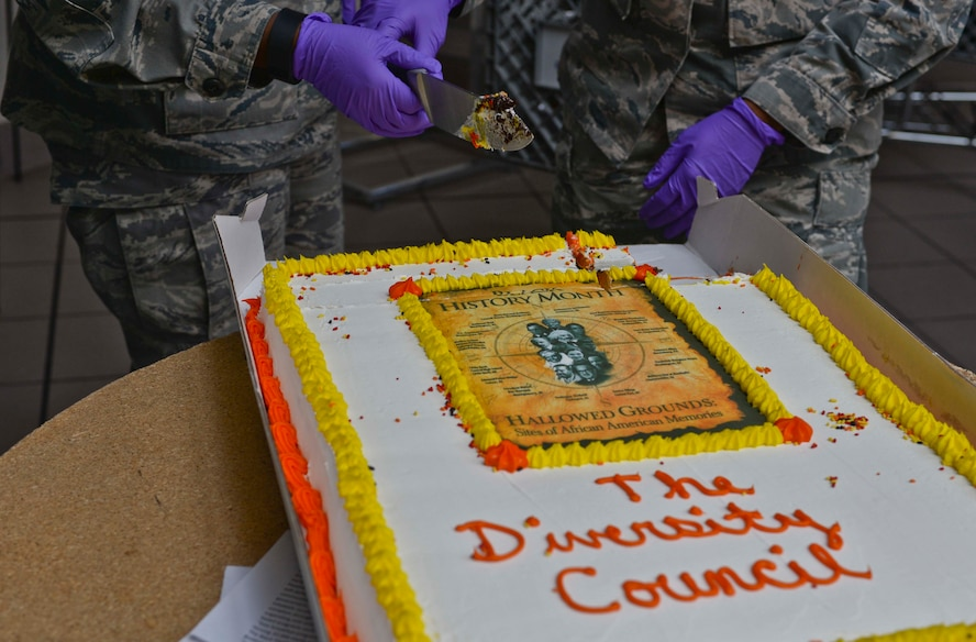 An Airman performs a cake cutting ceremony during a luncheon at Ellsworth Air Force Base, S.D., Feb. 24, 2016. The ceremony honored the accomplishments of African Americans for Black History Month and had more than 80 people in attendance. (U.S. Air Force photo by Airman Sadie Colbert/Released)