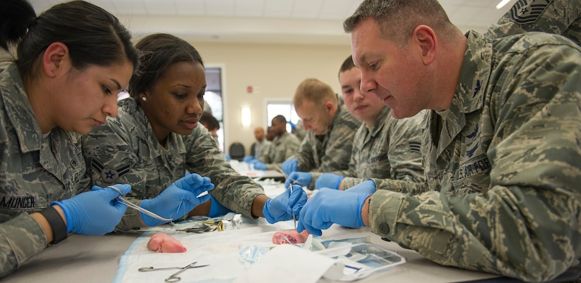 Airman 1st Class Ashley Madry, 628th Medical Group medical technician, helps Col. Robert Lyman, Joint Base Charleston commander, understand and learn how to suture on a pig's foot on JB Charleston – Air Base, S.C., on Feb. 17, 2016. This training session was the first time that JB Charleston's medical team interacted and worked with local civilian medical teams to advance their medical skills. (U.S. Air Force photo/Airman 1st Class Thomas T. Charlton)