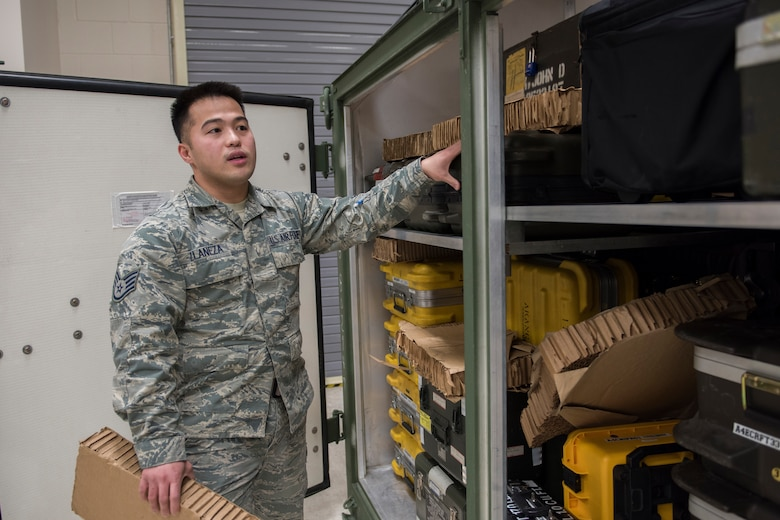 Staff Sgt. Mark Llaneza, an aviaonics technician with the 176th Maintenance Squadron, explains the importance of a shipping container housing the tools required to maintain the 176th Wing's C-130 Hercules aircraft here Feb. 5, 2016. The container will be packed to go with deployers down range in an upcoming mission. (U.S. Air National Guard photo by Tech. Sgt. N. Alicia Halla/Released)