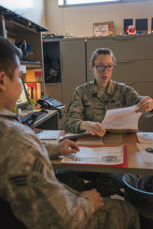 Tech. Sgt. Allison Cherry, the 176th Maintenance Group deployment manager, goes through 176th MXS-member Senior Airman Saechal's paperwork here Feb. 5, 2016, as he prepares to deploy. (U.S. Air National Guard photo by Tech. Sgt. N. Alicia Halla/Released)