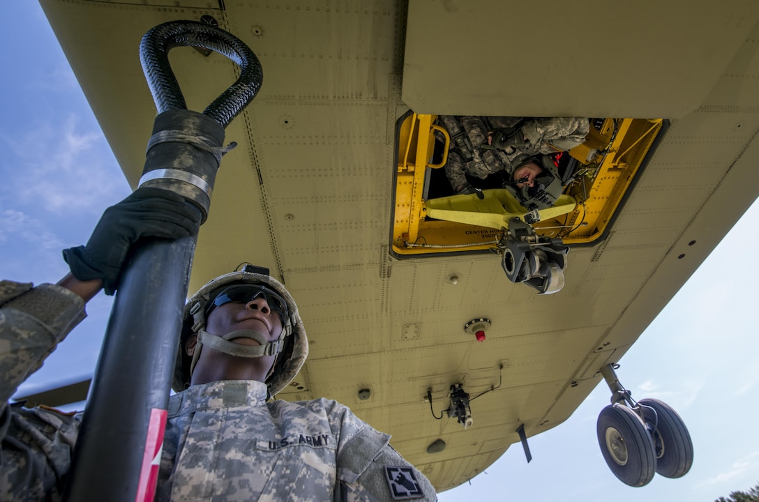 Spc. Christonio Hatten, a bridge crew member with the 502nd Engineer Company (Multi-Role Bridge), from Fort Knox, Ky., prepares to hook a sling to attach a boat bay to a Chinook during a sling load training operation with Army Reserve Soldiers at Fort Chaffee, Ark., July 31. Soldiers from various Army Reserve and active duty units trained together at River Assault, a bridging training exercise involving Army Engineers and other support elements to create a modular bridge on the water across the Arkansas River at Fort Chaffee, Ark. The entire training exercise lasted from July 28 to Aug. 4, 2015, involving one brigade headquarters, two battalions and 17 other units, to include bridging, sapper, mobility, construction and aviation companies. (U.S. Army photo by Master Sgt. Michel Sauret)