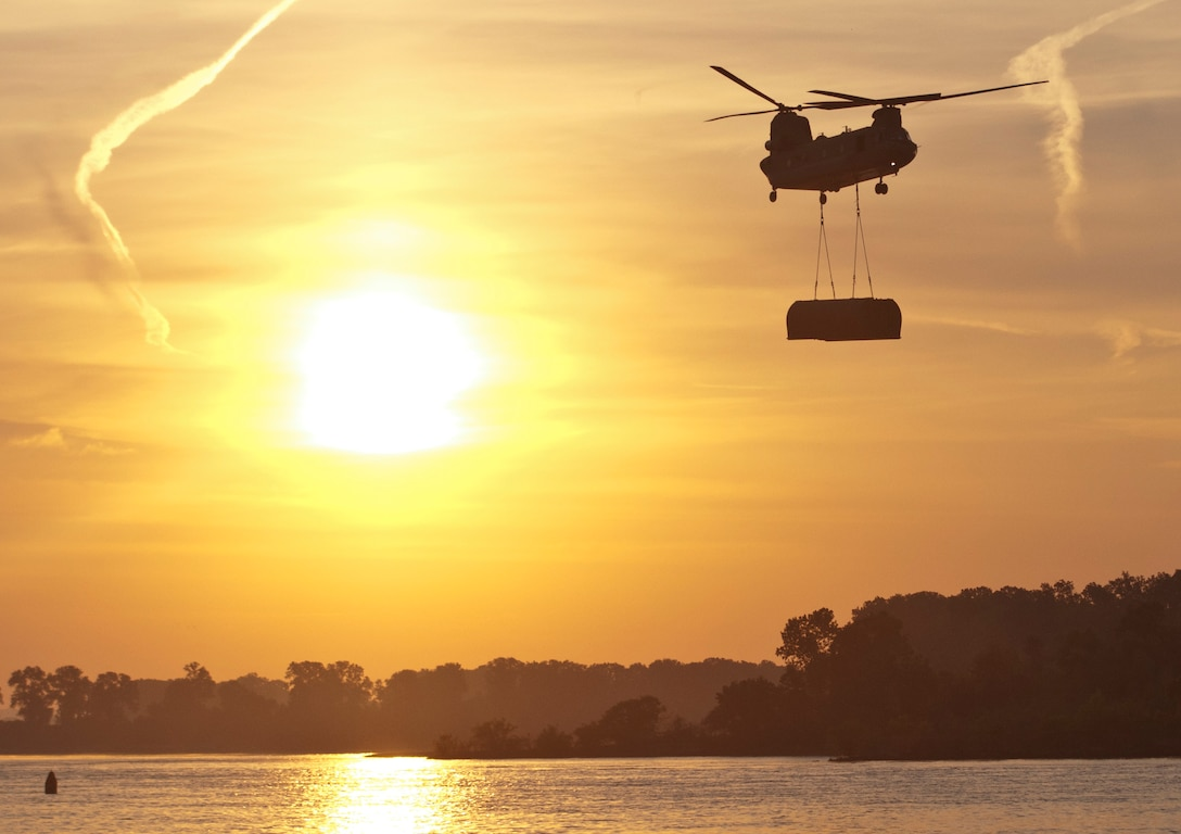 A CH-47 Chinook helicopter flown by Bravo Company, 7th Battalion, 158th Aviation Regiment, out of Fort Hood, Texas, transports a bridge bay to the Arkansas River Aug. 4 during the gap crossing, the culminating event of Operation River Assault 2015. Together, four Multi-Role Bridge Companies created an Improved Ribbon Bridge spanning 47 bays and 327 meters across the river. (U.S. Army photo by Staff Sgt. Debralee Best)