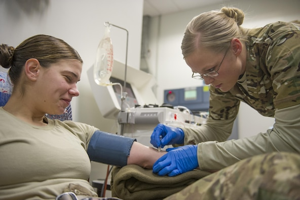 Spc. Lauren O'Neal, 153rd Blood Support Detachment medical laboratory technician, prepares Spc. Samantha Criscio, Guard Force, to give platelets at Craig Joint Theater Hospital on Bagram Airfield, Afghanistan, Dec. 31, 2015. In order to extract platelets, a critical life-saving blood component, apherisis machines are used to draw blood and return the unused portions to the donor. (U.S. Air Force photo/Tech. Sgt. Robert Cloys)