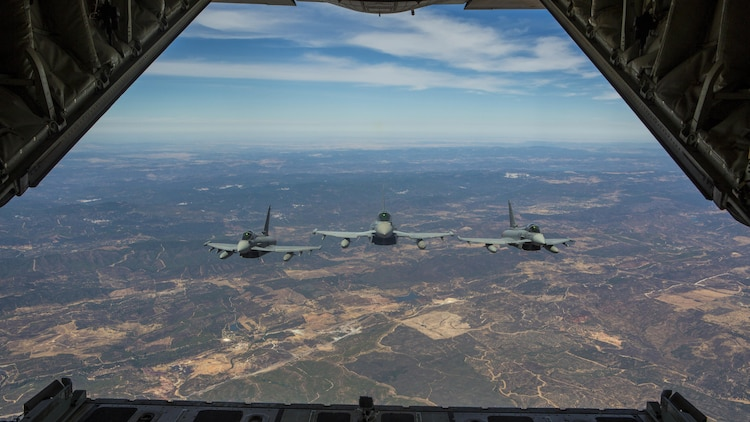 Three Eurofighter Typhoons with the Spanish Air Force escort a U.S. Marine Corps KC-130J Hercules during an aerial refueling mission, Aug. 13, in Spain. Bilateral exercises such as this one are how Spain and the U.S. foster one of the closest defense partnerships around the world.